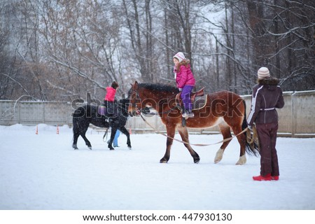Two girls riding on horses with instructors at the equestrian site in winter - stock photo