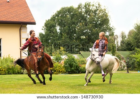 two girls riding pony on the summer green lawn