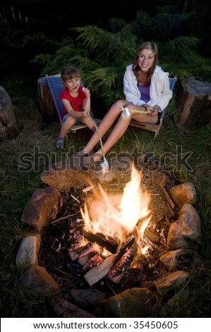 Two girls roasting marshmallows - stock photo