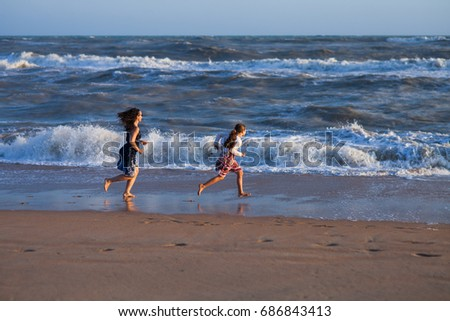 two girls run along the surf line on sandy beach
