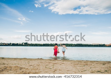 Two girls run into water