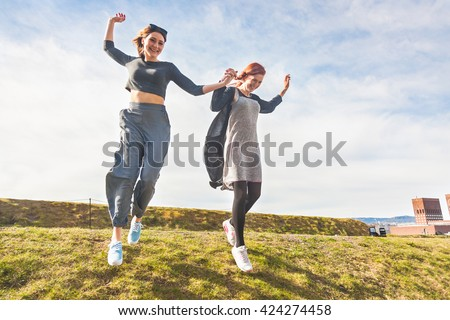 Two girls running down a hill in Oslo, holding hands and laughing. They are having fun together on a sunny spring day. Lifestyle and friendship concepts.