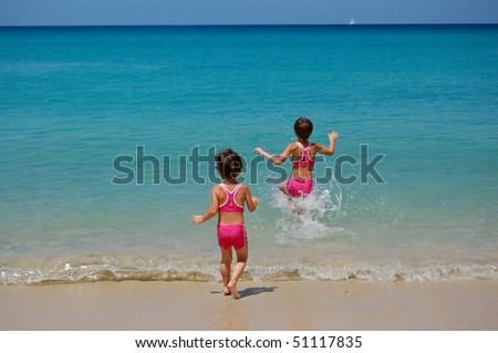 Two girls running to the sea - stock photo