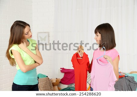 Two girls selecting and trying clothes at home - stock photo