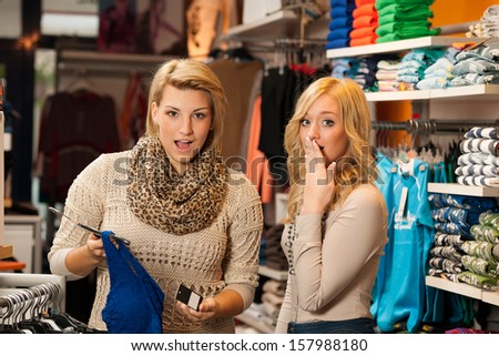 Two girls shocked by a price of clothes in a shop - women on shopping - stock photo