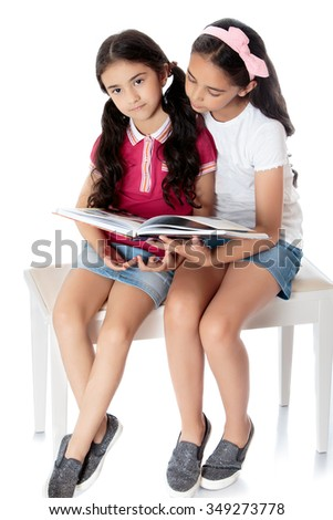 Two girls sisters reading the book . Girl sitting on white couch-Isolated on white background - stock photo