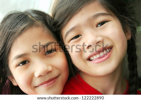 Two girls. Sisters smiling with heads together. Part Scandinavian, part Asian. - stock photo
