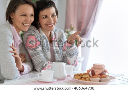 Two girls sit at a table and drinking tea - stock photo