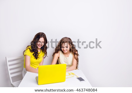 Two girls sit behind a laptop in yellow case. There is a smartphone on the table charging via yellow cable. Both girls are smiling and looking at the screen. One wears yellow t-shirt, another - dress.