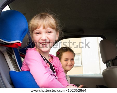 Two girls sit in a car on a child car chair