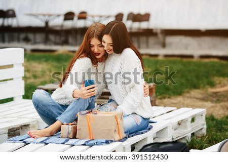 Two girls sit on a bench outside and shoot gifts for smartphone