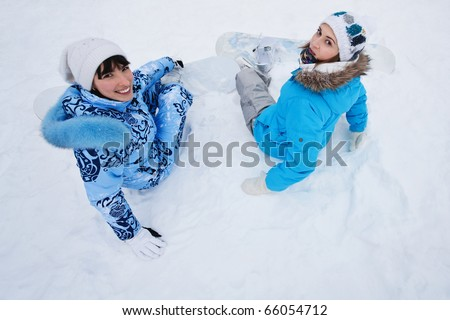 Two girls sit on snow and preparing to ride from the hill - stock photo