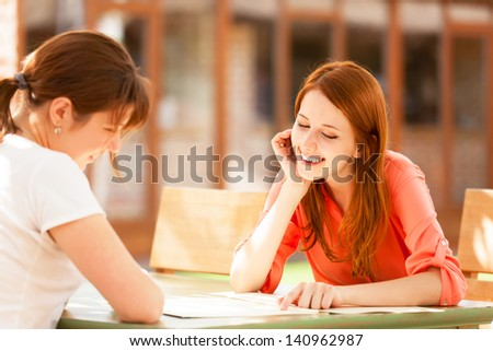 Two girls sitting in the cafe and looking in menu.