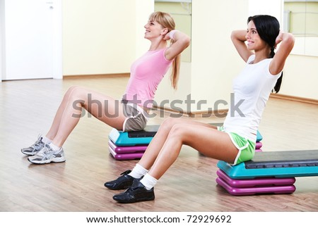 Two girls sitting in the gymnasium and practicing physical exercises