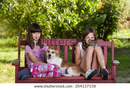 Two girls sitting on bench in park with dog and cat - stock photo