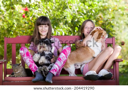 Two girls sitting on bench in park with dogs and cat - stock photo