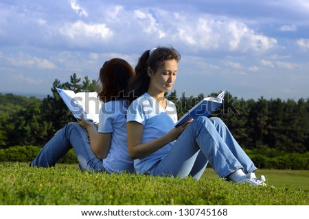 Two girls sitting on grass studying in the nature reading books outside - stock photo