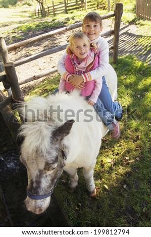 two girls sitting on pony - stock photo