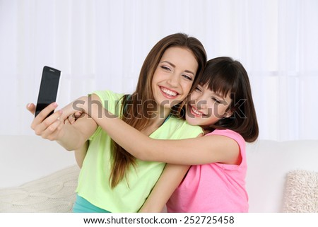 Two girls sitting on sofa and making photo on mobile phone - stock photo