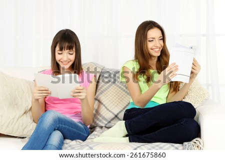 Two girls sitting on sofa and reading book on home interior background - stock photo