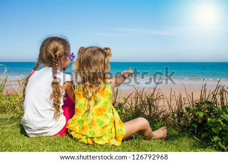 Two girls sitting on the beach and watching the sea - stock photo