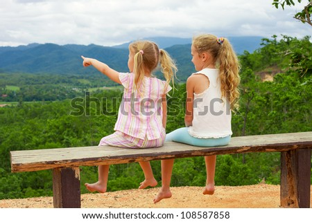 Two girls sitting on the bench against the backdrop of the mountains - stock photo