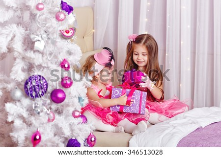Two girls sitting on the couch. The sisters show off the gifts to each other. New Year. Family celebration. Holiday and fun. Merry Christmas. 2017 - stock photo