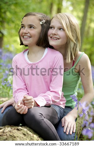 Two girls sitting together in a wood full of bluebells