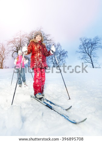 Two girls slide downhill on skies at a winter day - stock photo