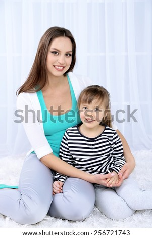 Two girls smiling on light background