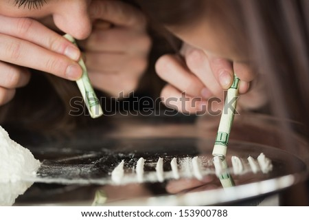 Two girls snorting an illegal substance with dollar bills off a mirror - stock photo