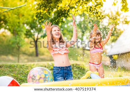 Two girls splashing water, sunny summer in the garden - stock photo