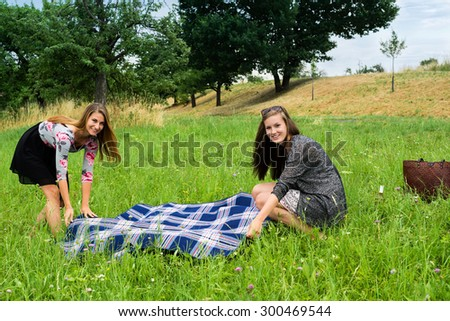 Two girls  spreading a blanket for a picnic in the green grass on a late summer day - stock photo
