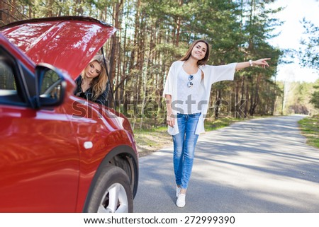 Two girls stand by the broken car on road - stock photo