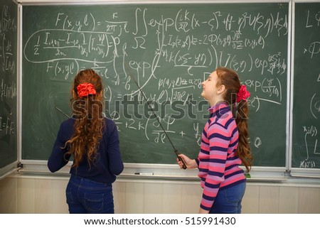 Two girls stand near blackboard with formulas in classroom and hold pointers