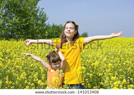 two girls standing in a field of flowers,best focus on T-shirts and hair - stock photo