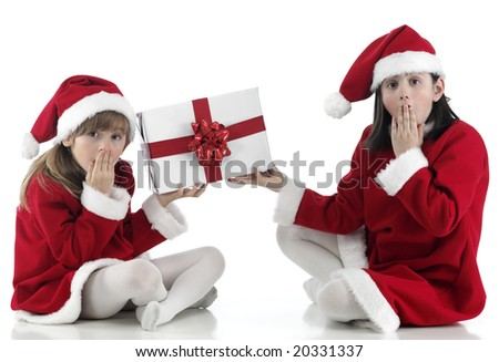 two girls surpraised with Christmas hat and presents - stock photo
