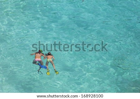 Two girls swimming while wearing snorkeling gear in water - stock photo