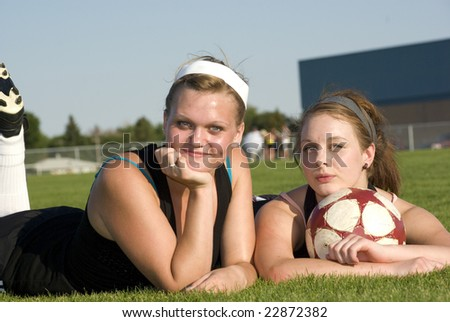 Two girls taking a break from playing soccer
