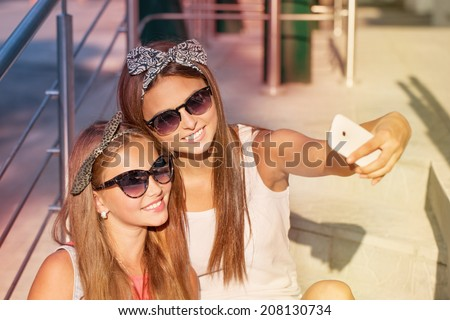 two girls  taking photos with a telephone - stock photo