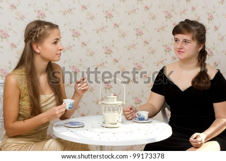 Two girls talking at a table in a cafe studio photography - stock photo