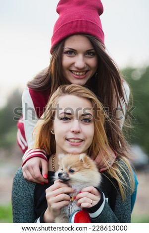two girls teens posing with puppy Pomeranian, portrait pyramid - stock photo