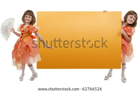 Two girls twins hold an empty yellow banner - stock photo