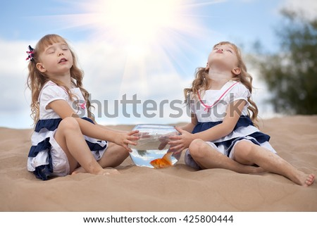 two girls twins keep a goldfish in an aquarium and dream - stock photo