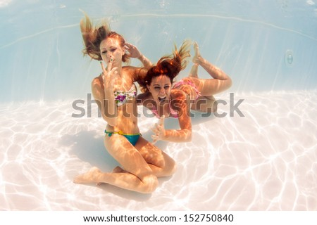 Two girls underwater portrait in swimming pool.  - stock photo