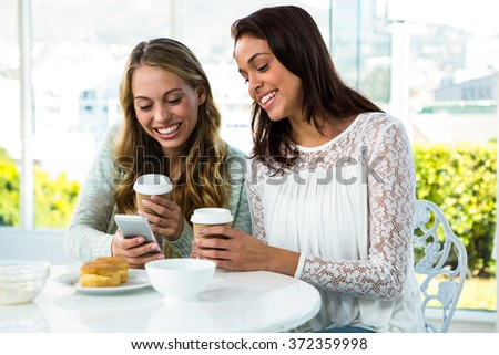 two girls use a phone while eating and drinking - stock photo