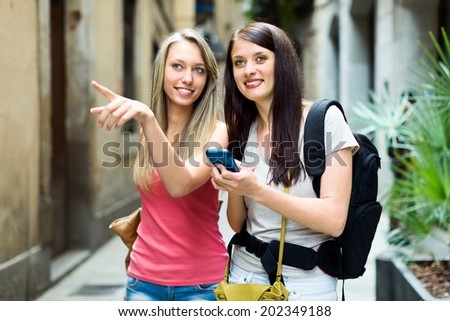 Two girls using  smartphone  for find a way in city - stock photo