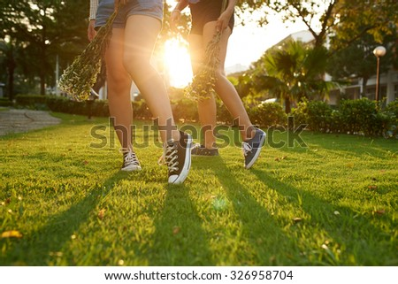 Two girls walking in park with flowers