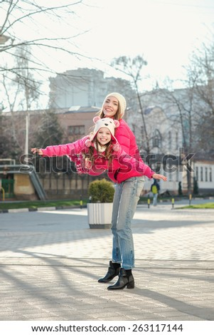 Two girls walking  in the city.  Adult and child, mother and daughter, two sisters walk on the street, spring. Facial expression. Casual style, sportswear, pink jackets. - stock photo