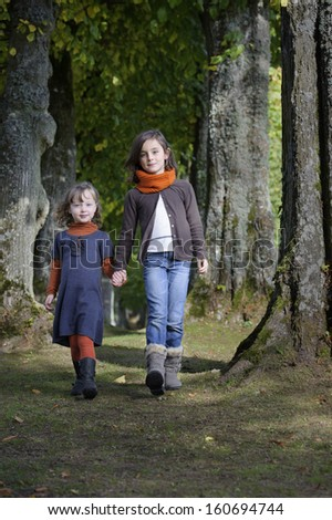 two girls walking on a path in the forest